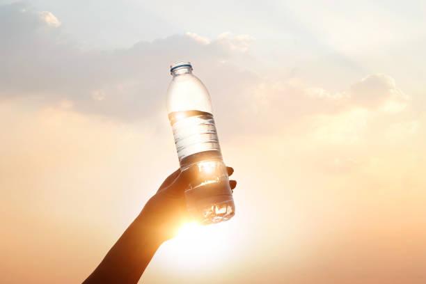 mano que sostiene el agua potable en fondo puesta de sol - foto de stock