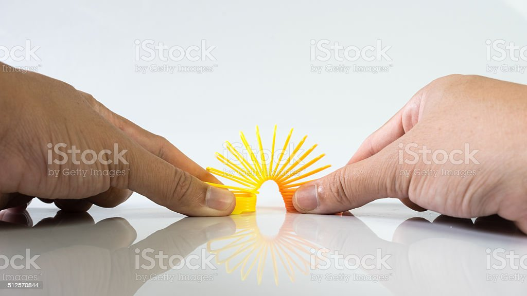 Hand holding elastic spring coil on empty background stock photo