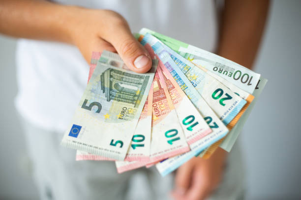 Hand holding euro banknotes Man hands holding euro banknotes. Selective focus european currency stock pictures, royalty-free photos & images