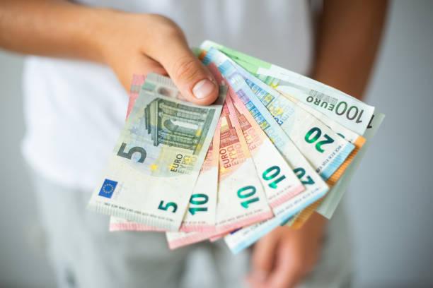 hand hält euro-scheine - europäische währung stock-fotos und bilder