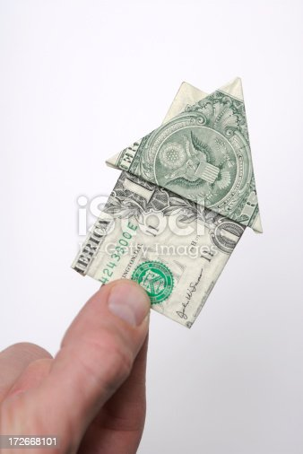 Hand holding onto a small house made from a folded dollar bill