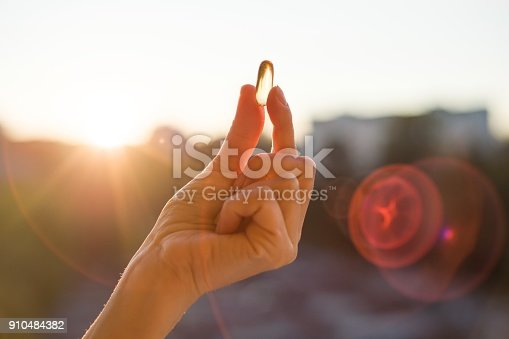 istock Hand holding fish oil Omega-3 capsules, urban sunset background. 910484382