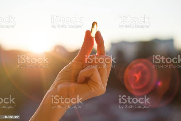 Hand holding fish oil omega3 capsules urban sunset background picture id910484382?b=1&k=6&m=910484382&s=612x612&h=sut5jpgz27kswjj8glse43fvdrskmitwa2j8n8gfviy=