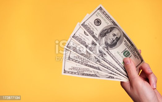 Woman holding 500 dollars against a yellow background.