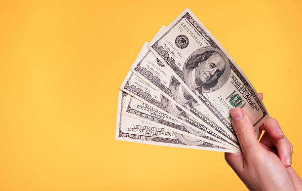A hand holding five $100 bills Woman holding 500 dollars against a yellow background. paper currency stock pictures, royalty-free photos & images