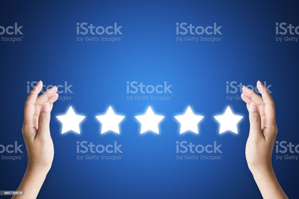 Hand holding five star symbol to increase rating of company with dark blue background, Copy space for text or headline stock photo