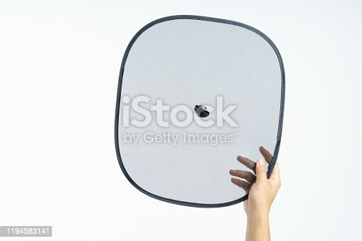 Hand holding folding sunshade retractable for windows or car windshield on white background