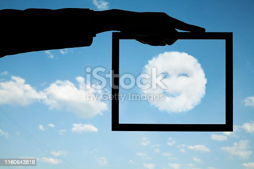 Hand holding frame around smiling winking cloud in blue sky