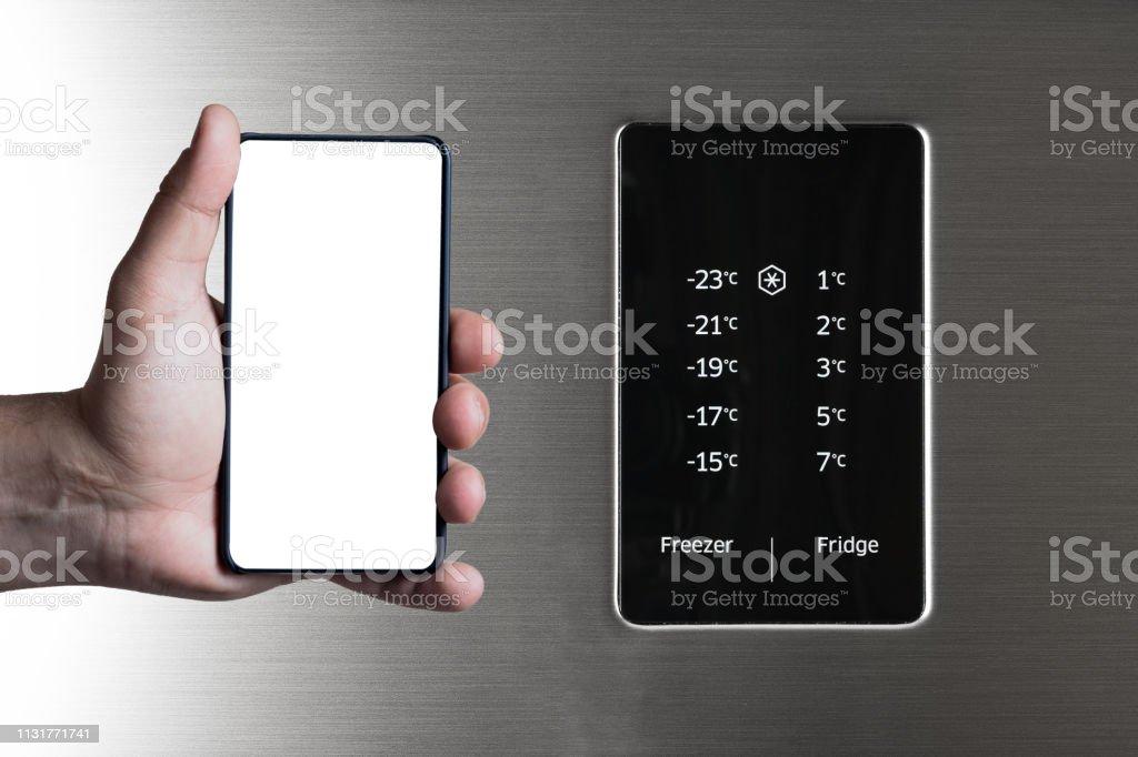 Hand holding frameless smartphone near fridge and freezer control panel. stock photo
