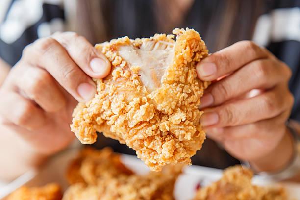 mão segurar frango frito e comer no restaurante - estaladiço imagens e fotografias de stock