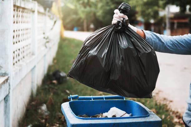 Hand hält Müllsack in den Müll – Foto