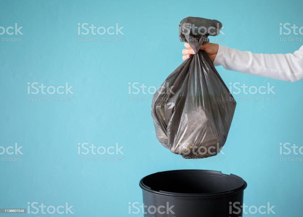 Hand hållande sopor i plast påse - Royaltyfri Avfallsbehållare Bildbanksbilder