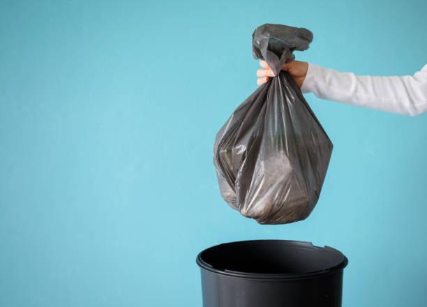 main retenant des ordures dans le sac en plastique - dechets photos et images de collection