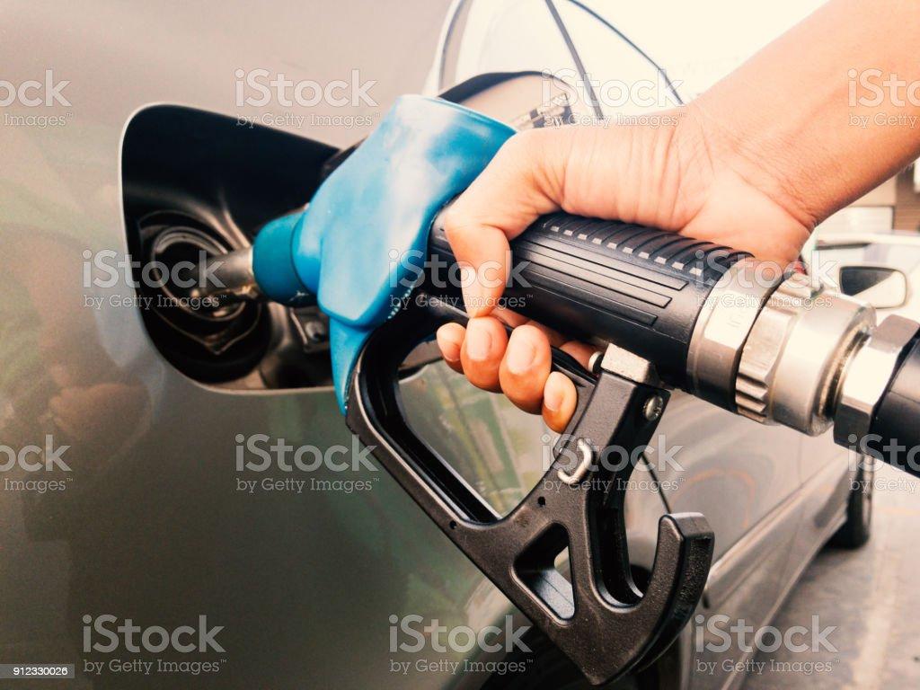 Hand holding gasoline nozzle stock photo
