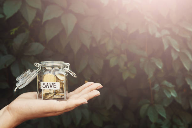Hand holding glass jar with coins with SAVE label stock photo