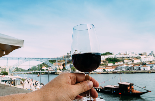 Hand holding glass of red wine in Porto, Portugal