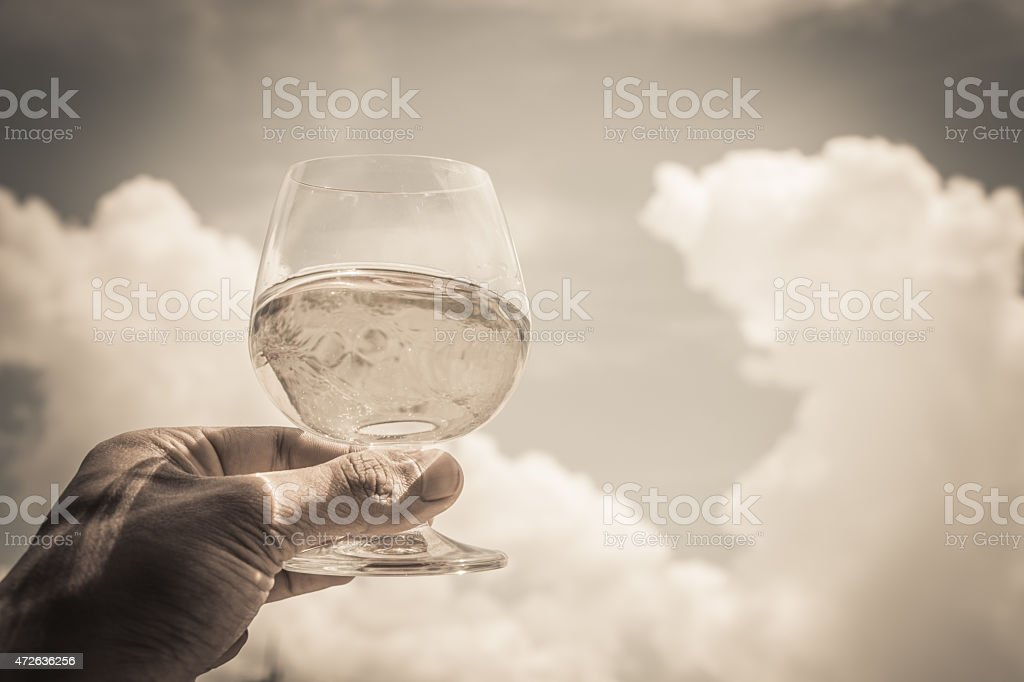 hand holding glass of water on sky stock photo