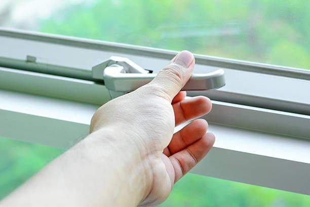 mão segurando a trava da alavanca janela de vidro - fechadura - fotografias e filmes do acervo