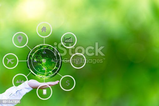 istock Hand holding globe with abstract global business cycle sketch on green background. Elements of this image furnished by NASA 691547936