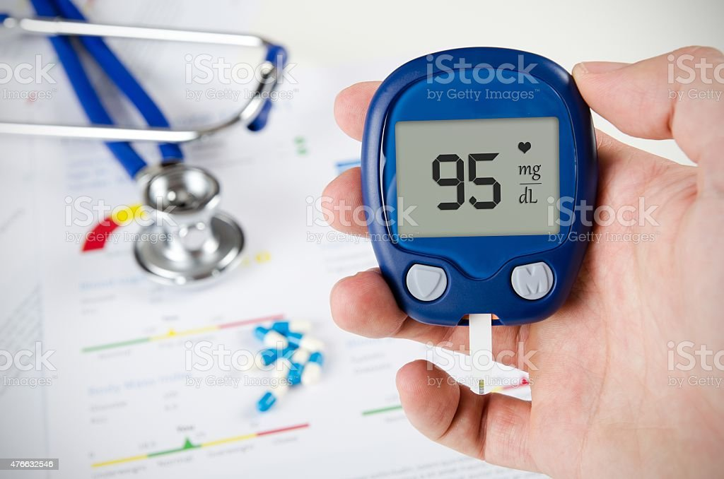 Hand holding glucometer. Stethoscope and pills in background stock photo