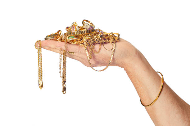 """Hand Holding Gold Jewelry Horizontal shot of a woman""""u2019s hand holding a pile of gold jewelry some of which is hanging down from her hand. She is also wearing a bracelet. Isolated on white.  Copy space. handful stock pictures, royalty-free photos & images"""
