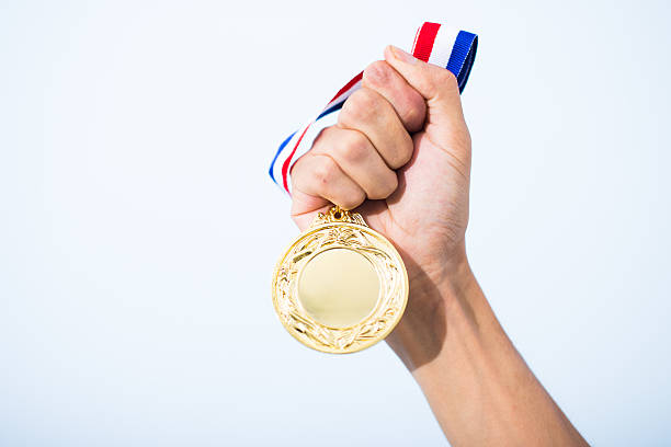 hand holding gold medal - medal stock photos and pictures