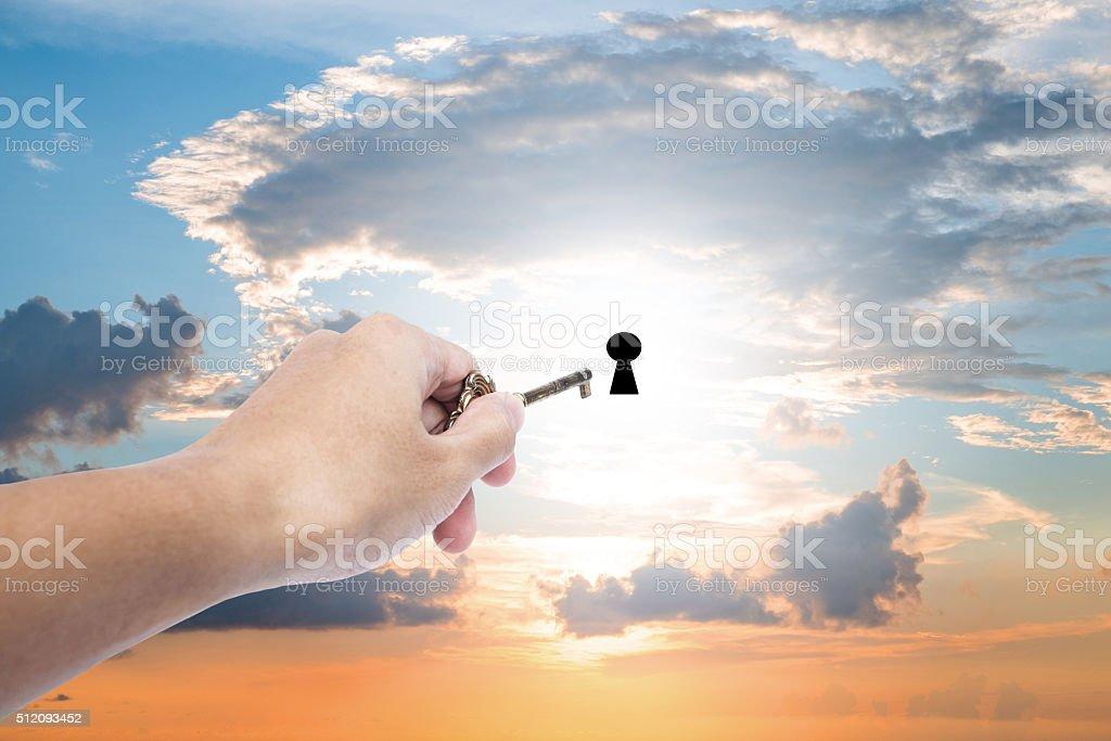 Hand holding golden key extending to unlock on sunset sky stock photo