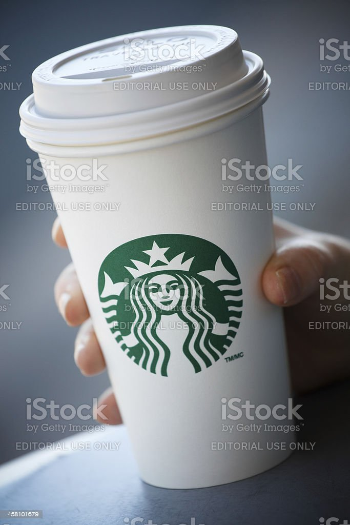 Hand holding grande Starbucks take out coffee cup stock photo