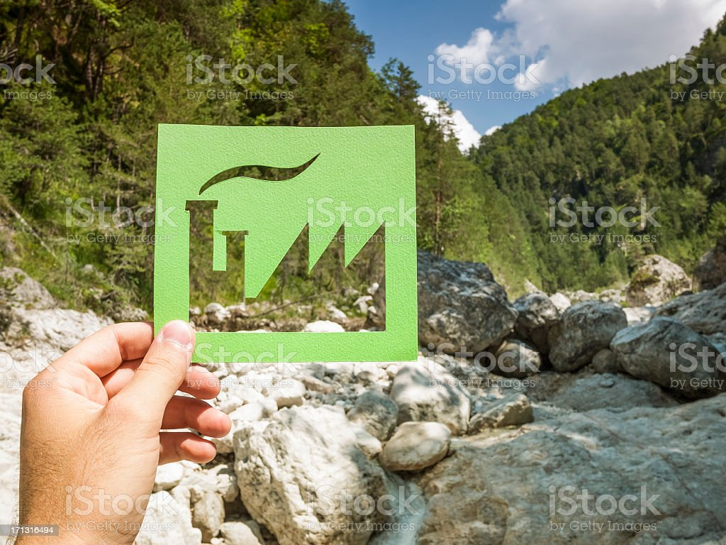 Hand holding green factory against nature royalty-free stock photo