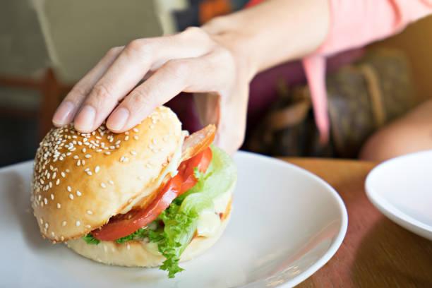 hambúrguer de exploração de mão.  conceito de fast-food. - junk food - fotografias e filmes do acervo