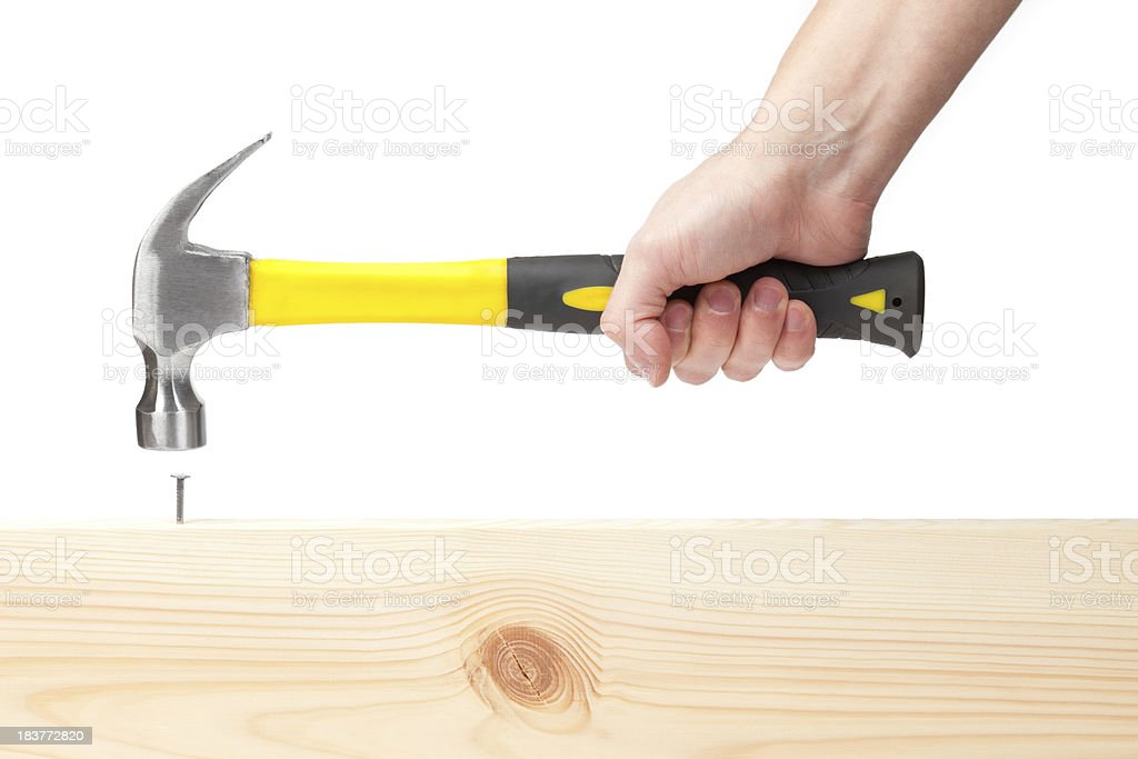 Hand holding hammer hitting a nail in wood stock photo