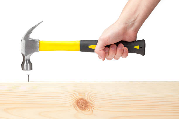 Hand holding hammer hitting a nail in wood Hammer in hand on white. This file is cleaned, retouched and contains  hammer stock pictures, royalty-free photos & images