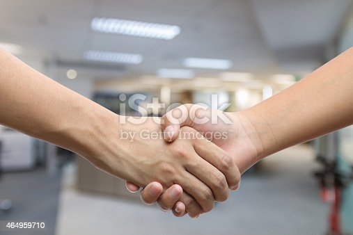 istock Hand holding hand isolated over office background 464959710