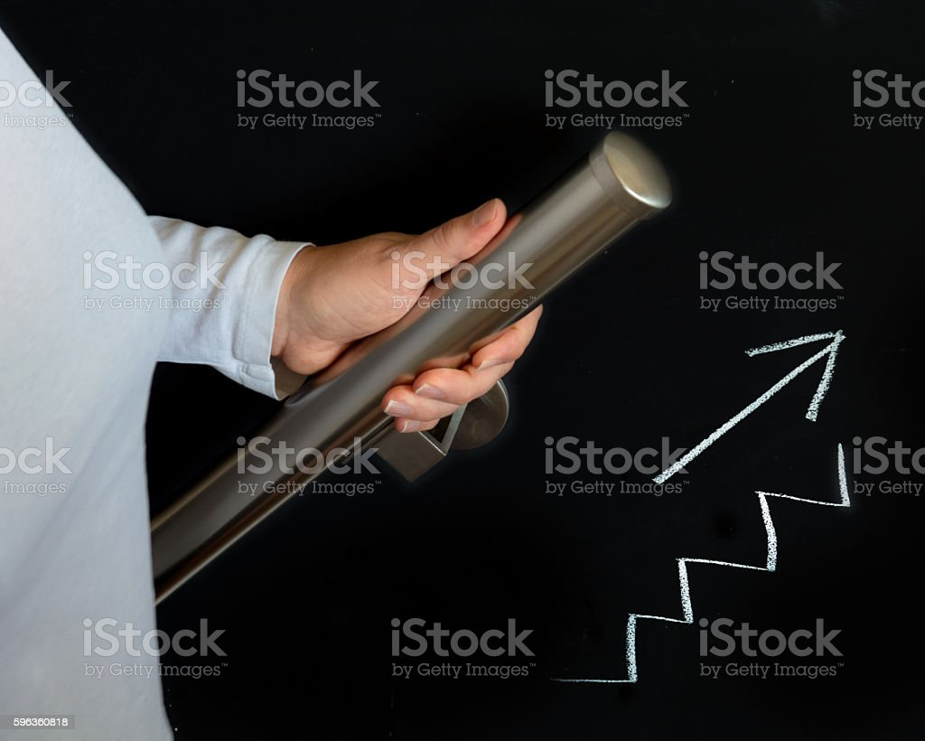 hand holding handrail on blackboard with drawing going up royalty-free stock photo