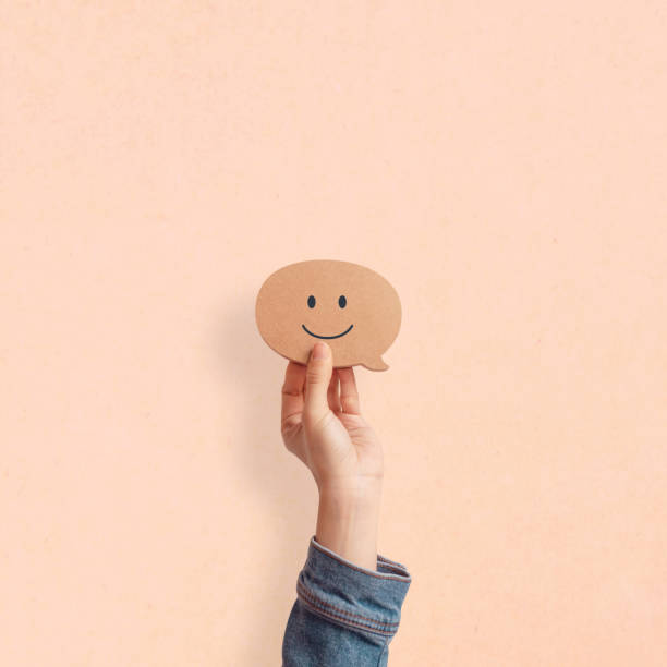 Hand holding happy face smiling comment in speech bubble on pastel background. stock photo