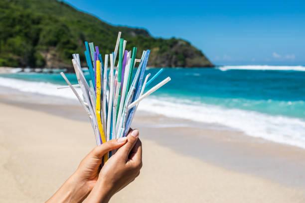 mucchio di cannucce di plastica usate sullo sfondo di spiaggia tropicale pulita e onde oceaniche - cannuccia foto e immagini stock