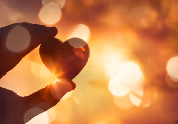 Hand holding heart against sparkling golden bokeh lights. stock photo