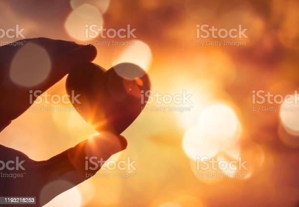 Photo of Hand holding heart against sparkling golden bokeh lights.