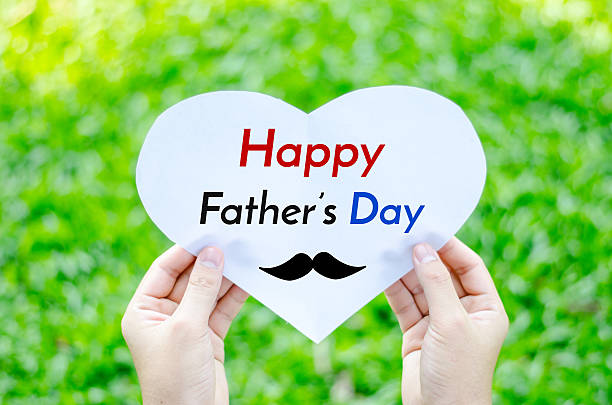 Hand holding heart paper with Happy Father's day text stock photo