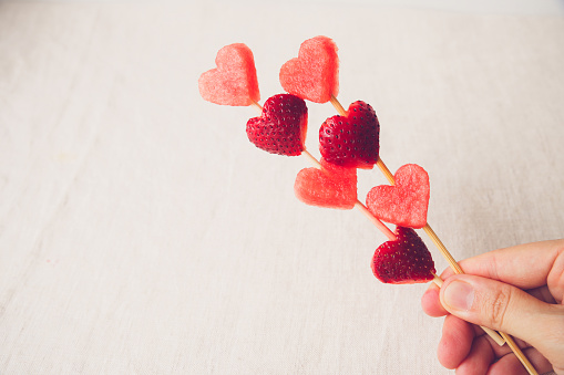 hand holding heart shape strawberry and watermelon fruit skewers