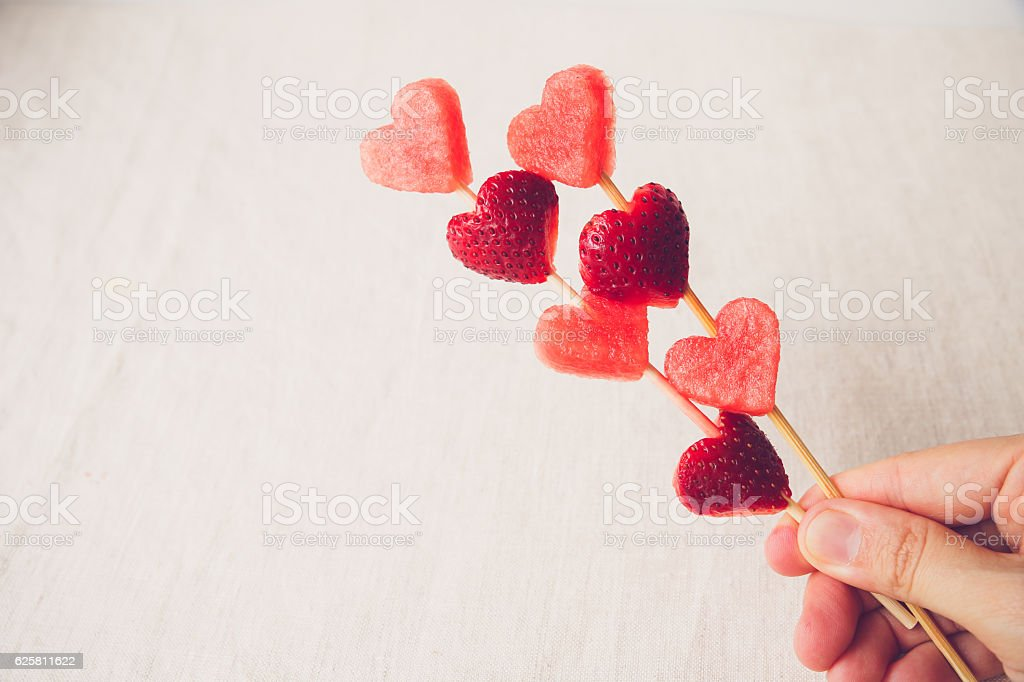 hand holding heart shape strawberry and watermelon fruit skewers stock photo