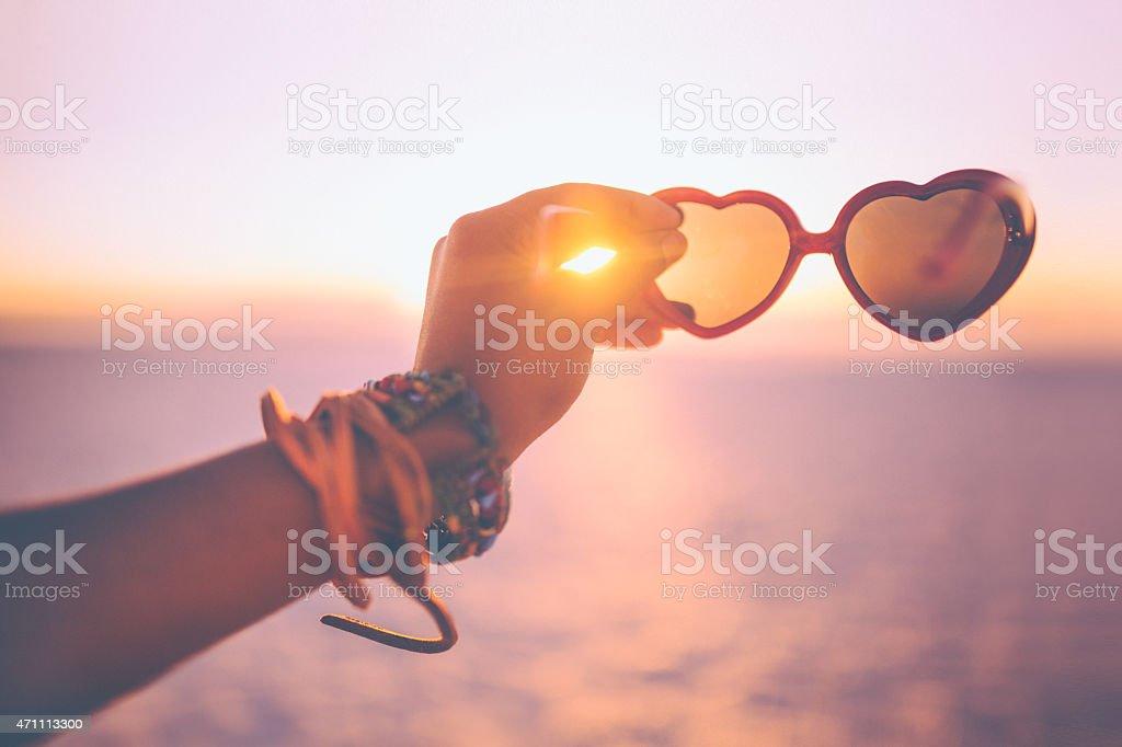 Hand holding heart-shaped sunglasses on a beach at sunset stock photo