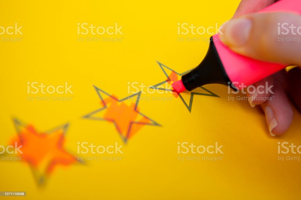 Hand holding highlighter and colouring rating stars Close-up of a hand holding a pink highlighter pen colouring in rating stars on yellow paper with copy space Color Image Stock Photo