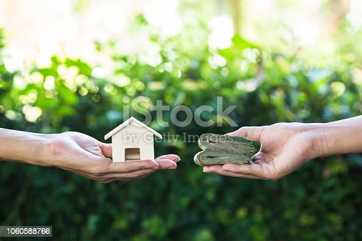 Home loan, lending, mortgage, transforming assets into cash concept : Hand holding home model change to money with green nature as background. Conceptual changing residence into cash.