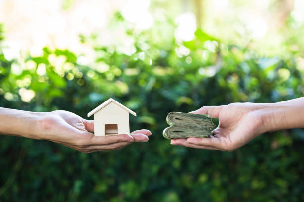 Hand holding home model change to money with green nature as background. Home loan, lending, mortgage, transforming assets into cash concept : Hand holding home model change to money with green nature as background. Conceptual changing residence into cash. borrowing stock pictures, royalty-free photos & images