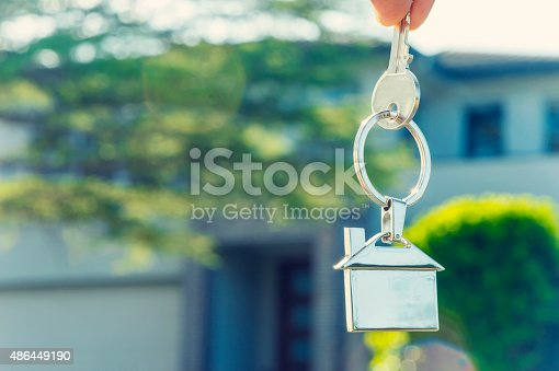 istock Hand holding house key in front of a large house. 486449190