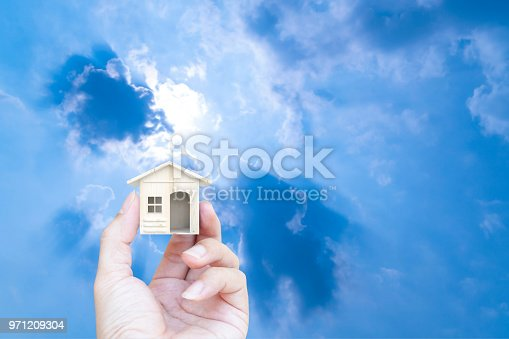 Hand holding house made wood on blue sky background