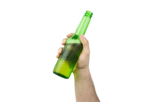 Mano que sostiene la botella de cerveza verde húmedo frío de hielo aislado sobre fondo blanco - foto de stock