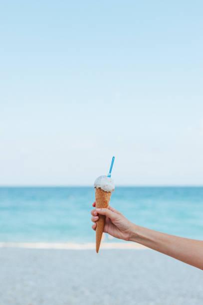 Hand holding ice cream and beach stock photo