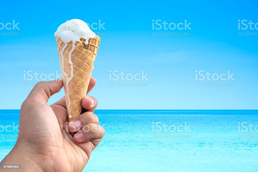 hand holding ice cream cone background the sea and blue sky. stock photo